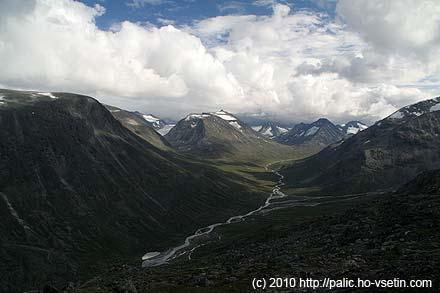 Horní část údolí Visdalen, dole malé jezero a u něj hotel Spiterstulen