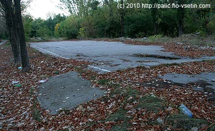 Polorozpadlé asfaltové hřiště s čarami na upravený nohejbal