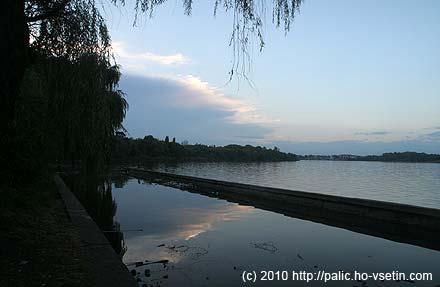 Plavecký bazén u břehu jezera, v pozadí přichází fronta